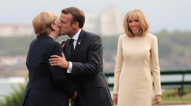 Presiden Prancis Emmanuel Macron (tengah) mencium Kanselir Jerman Angela Merkel (kiri) disaksikan istrinya Brigitte Macron (kanan) yang di KTT G7, Biarritz, Prancis, Sabtu (24/8/2019). KTT G7 beragenda pertahanan demokrasi, kesetaraan jender, pendidikan, dan lingkungan. (AP Photo/Markus Schreiber)