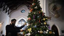 Seorang pria menghias pohon Natal di sebuah gereja di Peshawar, Pakistan barat laut (14/12/2020). Menyambut Natal, warga Pakistan mendekorasi rumah atau tempat ibadah agar lebih indah. (Xinhua/Umar Qayyum)