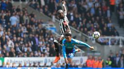 Duel pemain Arsenal, Joe Willock (bawah) dan pemain Newcastle United, Mohamed Diame pada lanjutan Premier League di St James' Park, Newcastle, (15/4/2018). Newcastle menang 2-1. (AFP/ Lindsey Parnaby)
