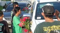 Aksi suporter Persebaya Surabaya, Bonek Mania, membagikan 1000 bunga mawar kepada kendaraan bermotor dengan plat N dan B di Surabaya, Sabtu (20/4/2019). (Bola.com/Aditya Wany)