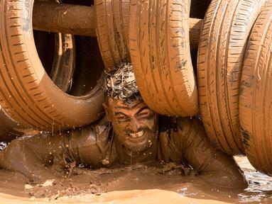 Ekspresi peserta dengan tubuh penuh lumpur saat mengikuti Mud Day di Tel Aviv, Israel (16/3). Dalam acara ini para peserta harus melewati rintangan sepanjang 13 kilometer. (AFP Photo/Jack Guez)