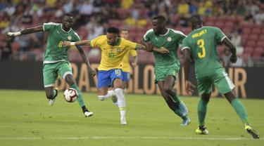 Penyerang Brasil, Neymar berusaha mengontrol bola dari kawalan tiga pemain Senegal pada pertandingan persahabatan di Stadion Nasional di Singapura (10/10/2019). Brasil bermain imbang dengan Senegal 1-1. (AFP Photo/Roslan Rahman)