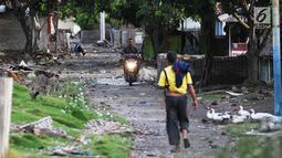 Pengendara motor melintas di dusun Regahan Lada, Pulau Sebesi, Lampung, Senin (31/12). Banyak warga dusun ini yang bertahan dan enggan meninggalkan rumahnya pascatsunami Selat Sunda pada 22 Desember lalu. (Liputan6.com/Herman Zakharia)