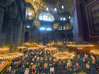 Jemaah mengenakan masker dan menerapkan jaga jarak untuk menghindari penularan COVID-19 saat melaksanakan salat Idul Adha di Hagia Sophia, Istanbul, Turki, Jumat (31/7/2020). Ini merupakan salat Idul Adha pertama di Hagia Sophia setelah dialihfungsikan dari museum menjadi masjid. (Pool via AP)