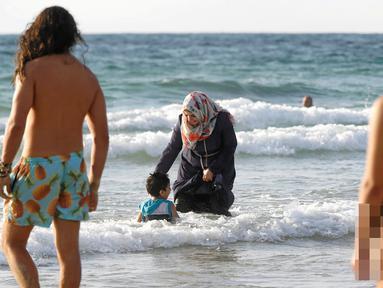 Seorang wanita Muslim bersama anaknya saat berada di pantai di Tel Aviv, Israel pada 22 Agustus 2016. Meski berada di pantai, wanita muslim ini tetap mengenakan jilbab dan busananya. (REUTERS / Baz Ratner)
