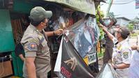 Anggota Satpol PP Kota Depok melakukan penertiban spanduk produk rokok di warung penjual rokok di Kota Depok, Selasa (24/8/2021). (Liputan6.com/Dicky Agung Prihanto)