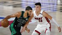Pebasket Boston Celtics, Jayson Tatum, berusaha melewati pebasket Miami Heat, Tyler Herro, pada gim pertama final Wilayah Timur playoff NBA di SPN World of Sports Complex, Selasa (15/9/2020). Heat menang dengan skor 117-114. (AP/Mark J. Terrill)
