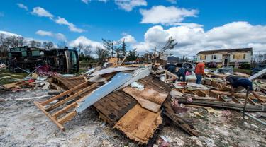 Warga dibantu relawan membersihkan puing-puing rumah mereka usai diterjang badai di Elon, Virginia (16/4). Badai disertai hujan lebat dan angin kencang melanda Virginia. (Jay Westcott/The News & Advance via AP)