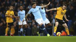 Bek Manchester City, Kyle Walker, berebut bola dengan pemain Wolverhampton Wanderers, Diogo Jota, pada laga Premier League di Stadion Etihad, Manchester, Senin (14/1). Manchester City menang 3-0 atas Wolverhampton Wanderers. (AP/Dave Thompson)