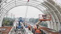 Pekerja menyelesaikan proyek pembangunan Light Rail Transit (LRT) Jabodebek di Stasiun LRT TMII, Jakarta, Senin (14/1). Stasiun LRT TMII dibangun dua lantai yang terdiri dari komersial dan pembelian tiket. (Liputan6.com/Faizal Fanani)