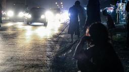 Sejumlah warga menunggu uang yang dilemparkan oleh pengguna jalan yang melintasi Jembatan Sewo, Jawa Barat, Minggu (2/7). Kegiatan ini dikenal dengan 'Sapu uang', yakni mengambil uang yang dilempar pengguna jalan. (Liputan6.com/Faizal Fanani)