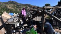 Seorang perempuan mencari sisa-sisa puing dari bangunan rumah yang rusak di Menggala, Lombok Utara, Rabu (8/8). Laporan terakhir mengatakan, gempa Lombok telah memakan 105 korban jiwa, dan lebih 70.000 orang kehilangan tempat tinggal. (AFP/ADEK BERRY)