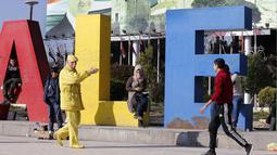 Abu Zakkour yang dijuluki 'Yellow Man' berjalan di alun-alun pusat Saadallah al-Jabiri, kota Suriah utara pada 11 Februari 2019. Ketika Zakkour menemukan sesuatu yang tidak cocok dengan kepribadian 'Yellow Man' -nya, ia tak segan untuk mengecat barang itu menjadi warna kuning. (LOUAI BESHARA/AFP)