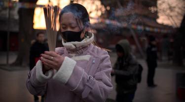 Seorang wanita memegang dupa berdoa di Kuil Lama di Beijing (5/2). Orang-orang China merayakan hari pertama Tahun Baru Imlek pada hari Selasa, Tahun Babi di zodiak Tiongkok dengan berdoa di kuil. (AP Photo/Mark Schiefelbein)