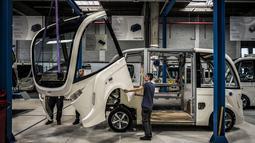 Pekerja memasang bagian depan bus tanpa pengemudi di pabrik NAVYA di Bron dekat Lyon, Prancis (23/4). Bus ini mengandalkan tenaga dari baterai charge yang mampu bertahan hidup antara rentan 8 hingga 24 jam. (AFP/Jean-Phoilippe Ksiazek)