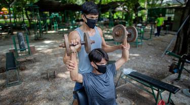 Dua pria berolahraga di gym luar ruangan di sebuah taman di Bangkok, Thailand, Rabu (10/6/2020). Kehidupan sehari-hari di ibukota kembali normal karena pemerintah Thailand terus melonggarkan pembatasan terkait dengan menjalankan bisnis di ibukota Bangkok. (AP Photo/Gemunu Amarasinghe)