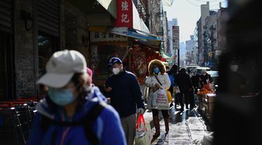 Orang-orang yang memakai masker berjalan di kawasan Chinatown di New York City pada 5 Februari 2021. Tahun Baru Imlek akan jatuh Jumat depan, 12 Februari, dan itu harusnya menjadi waktu tersibuk tahun ini untuk Chinatown, tetapi tidak pada tahun 2021 saat pandemi COVID-19 mewabah. (Angela Weiss/AFP)