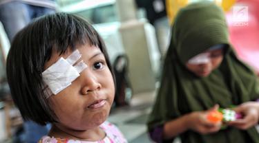 Seorang pasien anak diperban mata kanannya untuk mendapatkan bola mata palsu gratis di Klinik Ilyarsi Okularis, Villa Bintaro Indah, Tangsel, Selasa (15/5). Sebanyak 23 mata palsu dibagikan pada Gerakan 1.000 Mata Palsu Gratis. (Liputan6.com/Fery Pradolo)