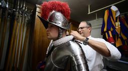 Seorang Pasukan Pengawal Swiss mengenakan seragam dan baju besi bersiap menghadiri upacara tahunan di Kota Vatikan (6/5). Mereka adalah pasukan yang khusus menjaga Vatikan dan Paus. (AFP/Filippo Monteforte)