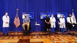 Wakil Presiden Amerika Serikat Mike Pence (kedua kiri) bersama sang istri Karen Pence (ketiga kiri) bersiap untuk menerima suntikan vaksin COVID-19 Pfizer-BioNTech di Gedung Putih, Washington, Jumat (18/12/2020). Acara vaksinasi itu disiarkan secara langsung di televsi AS. (AP Photo/Andrew Harnik)