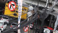 Instalasi kabel semrawut menjuntai di Jalan Dewi Sartika, Jakarta Timur, Sabtu (19/1). Selain mengganggu keindahan kota, kondisi tersebut juga berbahaya karena dapat memicu hubungan pendek arus listrik. (Liputan6.com/Immanuel Antonius)