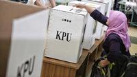 Penyandang disabilitas memasukkan surat suara ke dalam kotak saat simulasi Pemilu di Jakarta, Kamis (14/2). KPU menyediakan sejumlah fasilitas di TPS untuk penyandang disabilitas. (Liputan6.com/Faizal Fanani)