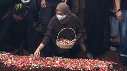 Adriyanti Firdasari, mantan pebulutangkis tunggal putri pelatnas PBSI yang juga sahabat dari Markis Kido memberikan penghormatan terakhir dengan menaburkan bunga. (Foto: Bola.com/Erwin Fitriansyah)