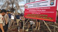 Penyidik Reskrimsus Polda Riau memasang plang di lahan perusahaan pembakar lahan karena memicu kabut asap. (Liputan6.com/M Syukur)