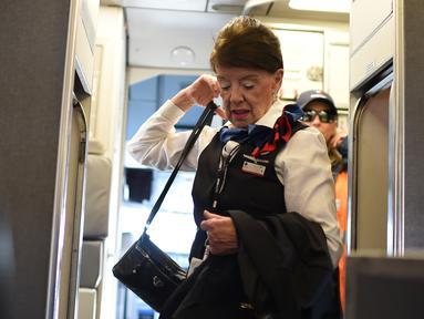 Pramugari tertua di maskapai American Airlines, Bette Nash membawa barang-barangnya sebelum melakukan penerbangan ke Boston di Bandara Ronald Reagan Washington di Arlington, Virginia (19/21). (AFP Photo/Eric Baradat)