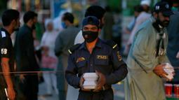 Seorang pria menerima kotak makanan dan minuman manis tradisional untuk berbuka puasa di Rawalpindi, Pakistan, Minggu, (3/5/2020). Umat Muslim di seluruh dunia sedang melaksanakan Ramadan untuk menahan diri dari makan, minum sejak subuh sampai senja. (AP/Anjum Naveed)