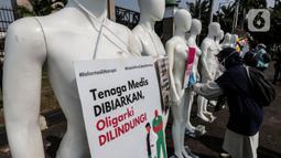 Aktivis Greenpeace Indonesia memasang poster pada puluhan maneken saat menggelar aksi damai di depan gerbang kompleks DPR, Jakarta Pusat, Senin (29/6/2020). Aksi tersebut dilakukan sebagai bentuk penolakan terhadap RUU Omnibus Law. (Liputan6.com/Johan Tallo)