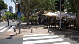 Warga Israel duduk di sebuah kedai kopi luar ruangan di Tel Aviv, Rabu (27/5/2020). Setelah lebih dari dua bulan ditutup untuk membendung penularan virus corona, restoran hingga kafe di Israel diizinkan dibuka kembali hari Rabu, 27 Mei. (AP Photo/Sebastian Scheiner)
