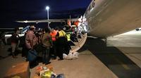 Ratusan calon penumpang berebut masuk ke pesawat Wings Air tujuan Makasar di Bandara Mutiara Palu, Selasa (2/10). Kemenhub membuka lalu lintas udara di pasca gempa pada hari Senin (1/10). (Liputan6.com/Fery Pradolo)