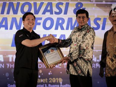 Perwakilan PT Surya Citra Media, Deputy Director Programming SCTV David Suwarto (kiri) menerima Penghargaan TOP IT & TELCO 2019 di Jakarta, Rabu (27/3). TOP IT & TELCO 2019 merupakan penghargaan untuk mendorong di kalangan bisnis, institusi pemerintah, BUMN dan lembaga. (Liputan6.com/Faizal Fanani)