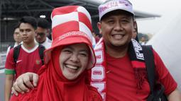 Dua suporter Timnas Indonesia tersenyum saat berada di Stadion Nasional, Singapura, Jumat (9/11). Indonesia akan melawan Singapura pada laga Piala AFF 2018. (Bola.com/M. Iqbal Ichsan)