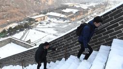 Dua wisatawan menaiki anak tangga saat menikmati liburan musim dingin di Tembok Besar China yang diselimuti salju di utara Beijing (6/1/2020). Salju yang turun tidak menyurutkan para wisatawan baik lokal maupun dari mancanegara untuk berkunjung ke Tembok Besar China. (AFP/Greg Baker)