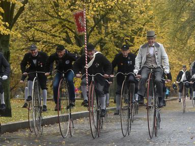 Para penggemar sepeda mengenakan kostum sejarah sambil mengendarai Penny Farthing atau dikenal sebagai sepeda roda tinggi selama kompetisi tradisonal 'One Mile Race' di Praha, Republik Ceko pada 3 November 2018. (Photo by Michal CIZEK / AFP)