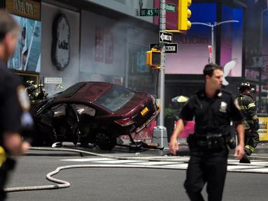 Petugas kepolisian berada dekat sebuah mobil yang menabrak para pejalan kaki di trotoar Times Square, New York, Kamis (18/5). Mobil tersebut melaju kencang ke arah jalur pejalan kaki dan menabrak kerumunan hingga menewaskan satu orang. (Jewel SAMAD/AFP)