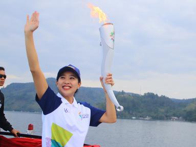 Artis Olivia Zalianty membawa obor Asian Games 2018 berkeliling Danau Toba di Sumatra Utara, Rabu (1/8). Obor Asian Games itu akan di bawa berlayar dengan kapal hias di Danau Toba dan bersepeda menuju pantai bebas Danau Toba. (Liputan6.com/Reza Perdana)