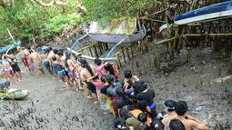 Warga berjalan menyusuri hutan mangrove saat mengikuti tradisi mandi lumpur atau mebuug-buugan di Desa Kedonganan, Denpasar, Bali, Jumat (8/3). Tradisi ini bertujuan menetralkan sifat buruk. (Sonny Tumbelaka/AFP)