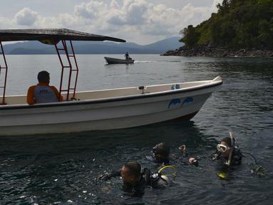 Wisatawan kembali dari selam scuba di lokasi penyelaman di dekat Iboih, pantai populer dan taman wisata di seberang teluk dari Sabang di pulau Weh, provinsi Aceh (6/10/2019). Pulau Weh (atau We) adalah pulau vulkanik kecil yang terletak di barat laut Pulau Sumatra. (AFP Photo/Chaideer Mahyuddin)
