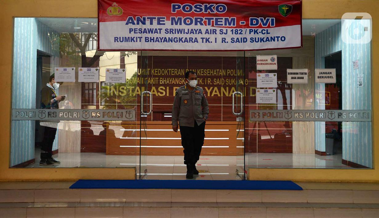 Seorang polisi berjalan di Posko Ante Mortem-DVI RS Polri Jakarta, Selasa (12/1/2021). Hingga saat ini, tim DVI masih mengumpulkan sampel DNA penumpang pesawat Sriwijaya Air SJ 182 yang jatuh di perairan Kepualauan Seribu. (merdeka.com/Imam Buhori)
