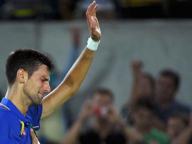 Atlet tenis asal serbia sekaligus petenis nomor satu dunia, Novak Djokovic menangis usai kalah dalam pertandingan babak pertama tenis yang digelar di Olympic Tennis Centre-CC, Rio De Janeiro,Brasil,  Senin (8/8). (REUTERS / Toby Melville)