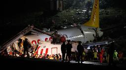 Tim penyelamat dan petugas pemadam kebakaran bekerja setelah sebuah pesawat tergelincir di landasan pacu Bandara Sabiha Gokcen, Istanbul, Turki, Rabu (5/2/2020). Pesawat Boeing 737-86J yang membawa 177 penumpang tersebut terbakar dan meledak usai tergelincir di landasan pacu. (AP Photo/Emrah Gurel)