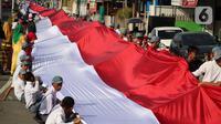 Pelajar SMA membentangkan bendera Merah Putih sepanjang 2,3 kilometer di Jalan Panjaitan dan Jalan Nani Wartabone, Gorontalo, Kamis (23/1/2020). Para pelajar menyanyikan lagu Indonesia Raya sambil membentangkan bendera Merah Putih. (Liputan6.com/Arfandi Ibrahim)