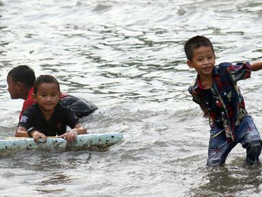 Sejumlah anak-anak bermain di genangan air akibat banjir rob di kawasan pintu masuk Pelabuhan Nizam Zachman, Muara Baru, Jakarta, Jumat (5/6/2020). Banjir rob di Pelabuhan Muara Baru tersebut terjadi akibat cuaca ekstrem serta pasang air laut. (Liputan6.com/Helmi Fithriansyah)