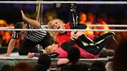Pegulat Lacey Evans berusaha mengunci lawannya, Natalya Neidhart pada pertarungan World Wrestling Entertainment (WWE) untuk perempuan di Stadion Internasional King Fahd, Riyadh, 31 Oktober 2019. Kerajaan Arab Saudi untuk pertama kalinya menggelar pertandingan gulat WWE perempuan. (AP/Amr Nabil)