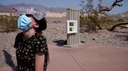 Katie Moore mendinginkan kepalanya dengan sekantong es di Taman Nasional Death Valley, California, AS, Senin (17/8/2020). Suhu terpanas di dunia terpantau terjadi di Taman Nasional Death Valley yang mencapai 130 derajat Fahrenheit (54,4 derajat Celcius) pada Minggu 16 Agustus. (AP Photo/John Locher)