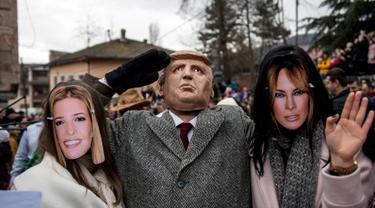 Peserta berpakaian seperti Ivanka Trump, Presiden AS Donald Trump dan Melania Trump saat mengikuti karnaval di desa Vevcani, Macedonia (13/1). Karnaval Vevcani ini selalu digelar setiap tahunnya dan telah berusia 1,400 tahun.(AFP Photo/Robert Atanasovski)