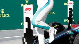 Lewis Hamilton melompat dari mobilnya merayakan kemenagan menjuarai GP Hungaria di Sirkuit Hungaroring, Mogyorod, (29/7). Kemenangan ini sekaligus menempatkan Hamilton berada di puncak klasemen. (AP Photo/Laszlo Balogh)